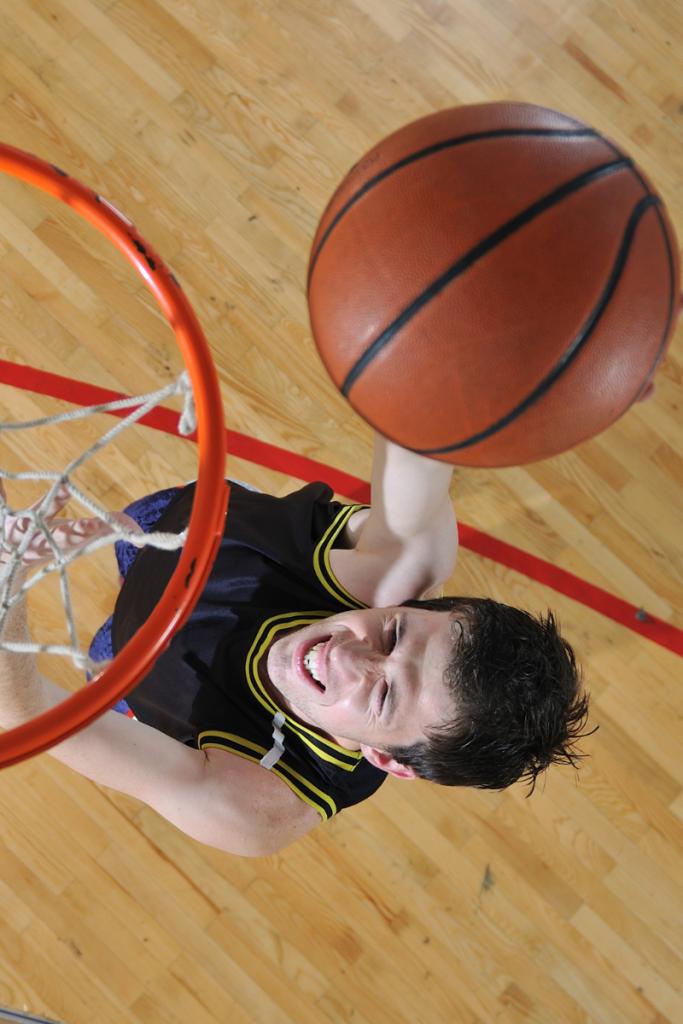 Teen basketball player dunking a basketball