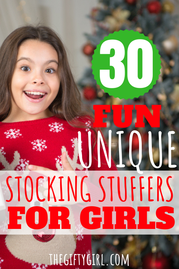 A Christmas Tree in the background with a smiling girl in a reindeer sweater. Text overlay says 30 fun unique stocking stuffers for girls.