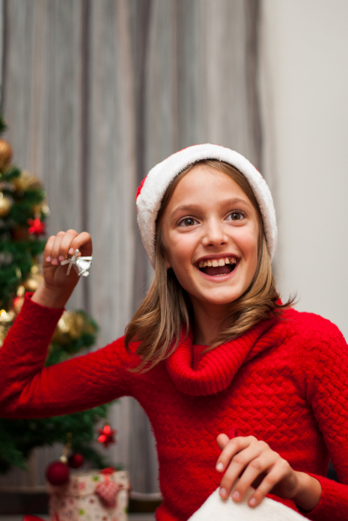 A happy girl in a red turtleneck with a santa hat. She is smiling and holding a bell. Maybe she is excited because of the stocking stuffers for girls she found in her stocking.