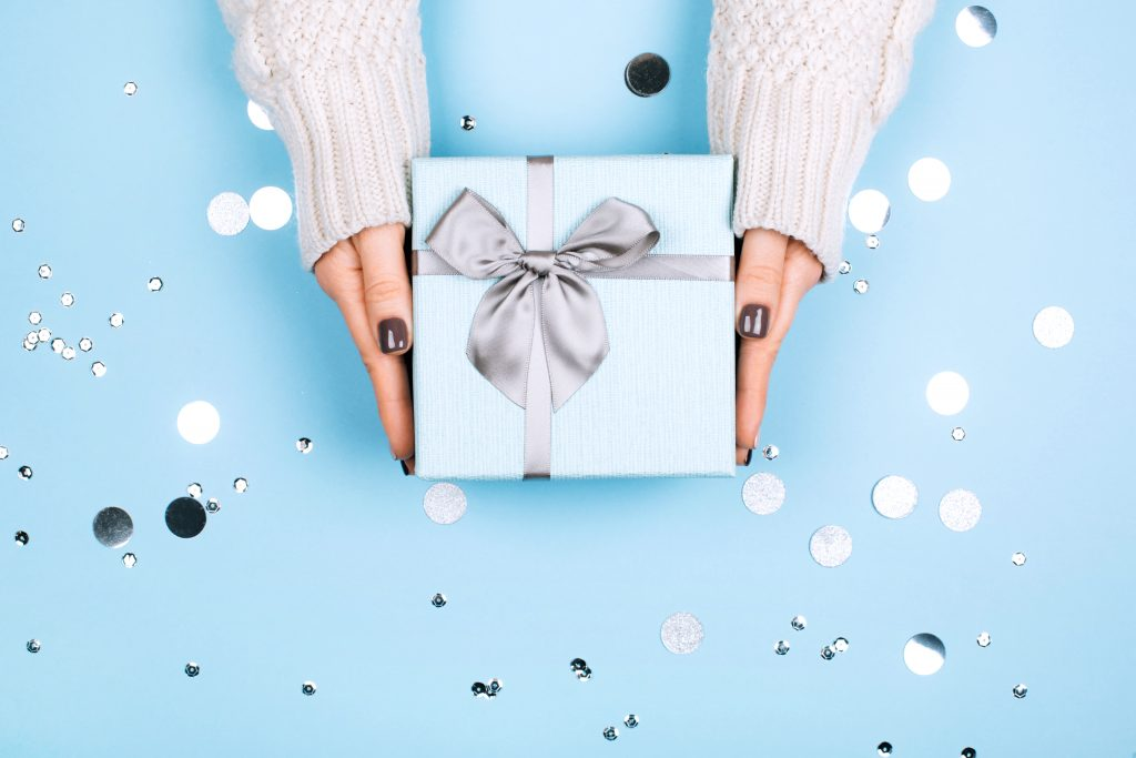 blue background with silver confetti. A woman's hands with a dark manicure holding a blue gift with a silver ribbon.