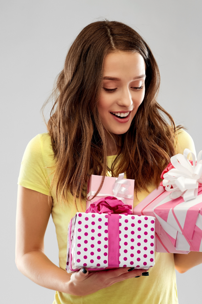 Photo of teenage girl in a yellow shirt holding two gifts wrapped in pink wrapping paper