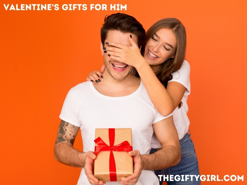 """Orange backdrop with a man sitting down with a present in his hands. A woman is standing behind him wit her hand over his eyes. They are both happy. Text overlay says """"Valentine's Gifts for Him TheGiftyGirl.com"""""""