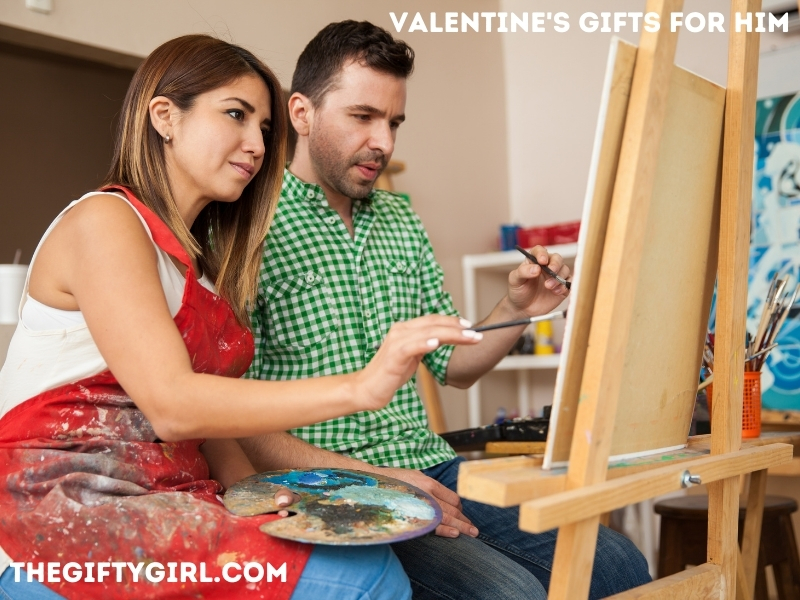 """Image of a couple sitting next to each other painting a picture together with overlay text saying """"Valentine's Gifts for Him TheGiftyGirl.com"""""""