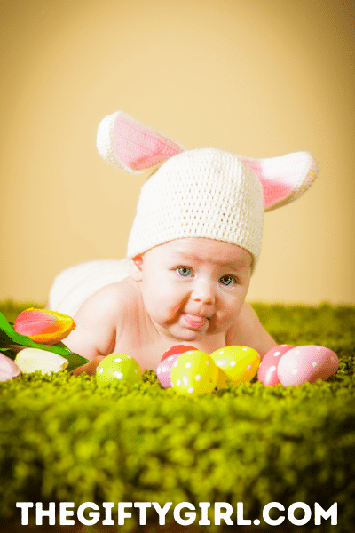 A young baby is lying on green carpet that has Easter eggs and tulips on it. Baby is wearing a crocheted bunny hat with ears and lying on his/her tummy looking at the camera.