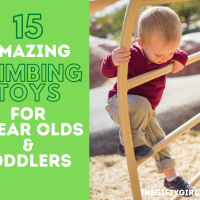 A small toddler boy in a red sweater and brown pants concentrates as he climbs up an outdoor metal ladder. Text overlay says 15 amazing climbing toys for 1 year olds and toddlers Thegiftygirl.com