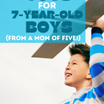 Photo of a 7-year-old boy holding an airplane with text overlay that says 51 of the best toys for 7 year old boys from a mom of five thegiftygirl dot com